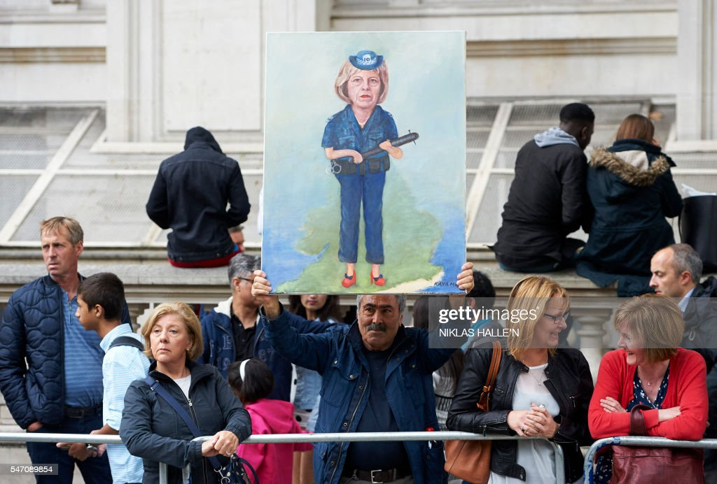 Political painter and artist Kaya Mar displays a painting depicting new British Prime Minister Theresa May outside Downing street in central London on July 13, 2016, on the day new British Prime Minister Theresa May takes over at number 10. Theresa May took office as Britain's second female prime minister on July 13 charged with guiding the UK out of the European Union after a deeply devisive referendum campaign ended with Britain voting to leave and David Cameron resigning. / AFP / NIKLAS HALLE'N