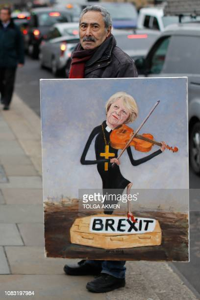Political satire artist Kaya Mar poses with one of his artworks depicting Britain's Prime Minister Theresa May outside the Houses of Parliament in...