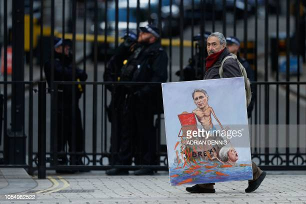 Political satire artist Kaya Mar walks with a painting depicting Britain's Chancellor of the Exchequer Philip Hammond and Britain's Prime Minister...