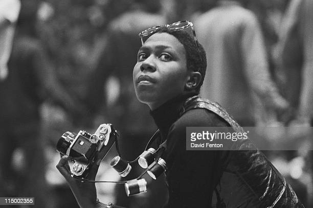 Political and social activist and Black Panther member Afeni Shakur looks up while photographing the scene during a rally in support of the Panther...