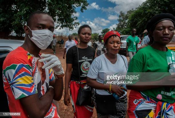 Political supporter wears a face mask and gloves as a preventive measure against the COVID-19 coronavirus while attending an event of a signed an...