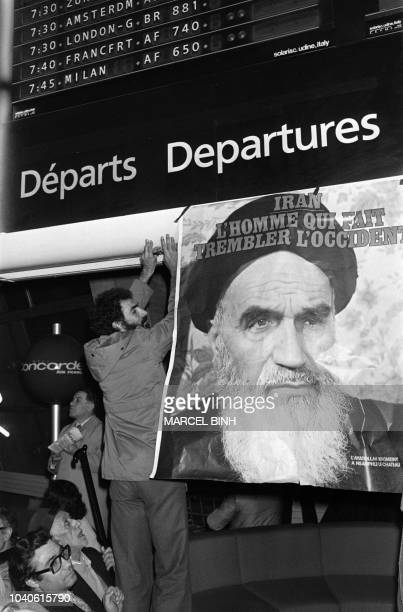 Political supporters display a poster of Iranian opposition leader in exile ayatollah Ruhollah Khomeiny at Roissy airport near Paris on January 31...