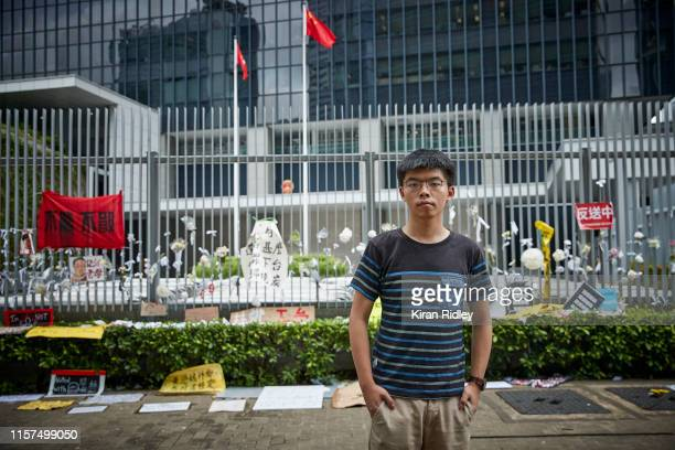 Politician and student activist Joshua Wong photographed against a wall of posters demonstrating against the Hong Kong government's unpopular...