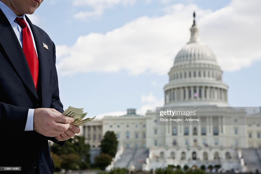 A politician counting money in front of the US Capitol Building : Stock Photo