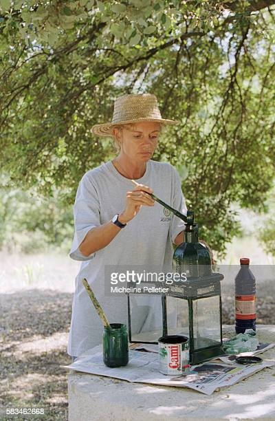 Politician Elisabeth Guigou paints a lantern while vacationing in the Vaucluse region of France