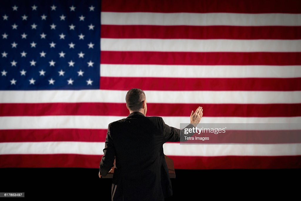 Politician giving speech with American flag in background : Stock Photo
