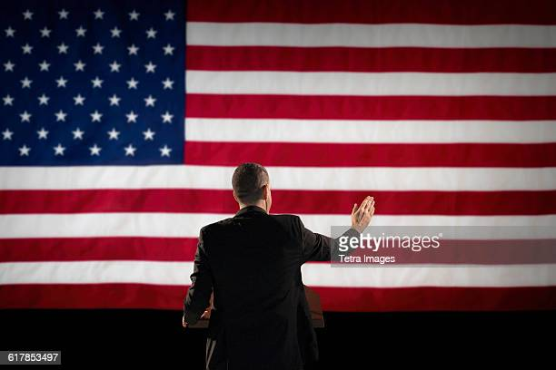 Politician giving speech with American flag in background