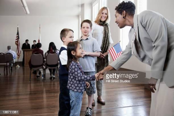 politician greeting children at political gathering - lokales regierungsgebäude stock-fotos und bilder