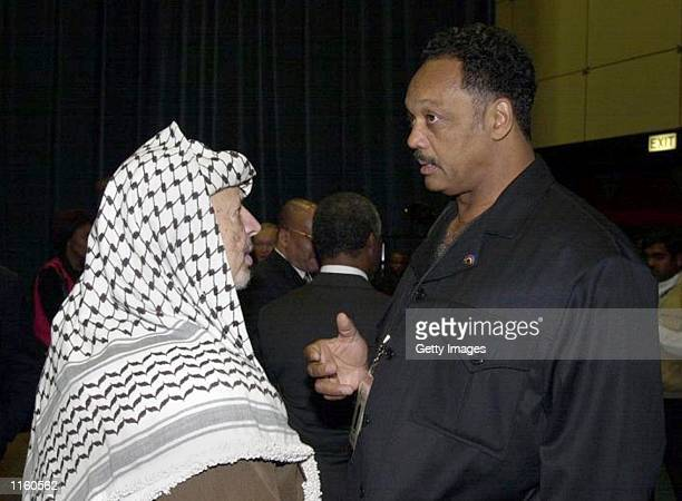 Politician Jesse Jackson talks with Palestinian leader Yasser Arafat during the opening session of the World Conference Against Racism August 31,...