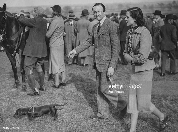 Politician John Profumo and Mrs A Cameron walking the course at Whaddon Chase pointtopoint at Nash near Bletchley England March 13th 1938