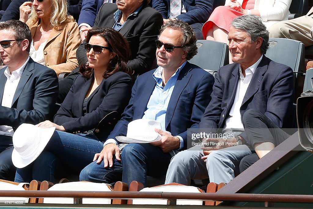 Politician Luc Chatel sitting between his companion Mahnaz Hatami (L) and Mayor of Deauville Philippe Augier (R) attend the 2015 Roland Garros French Tennis Open - Day 2, on May 25, 2015 in Paris, France.