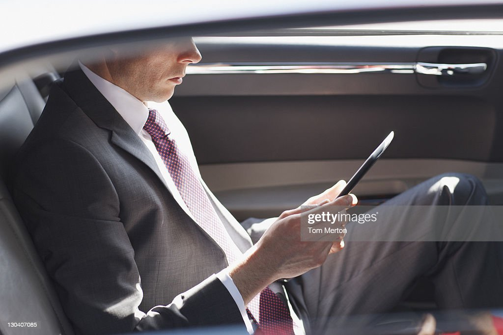 Politician reading in backseat of car : Stock Photo