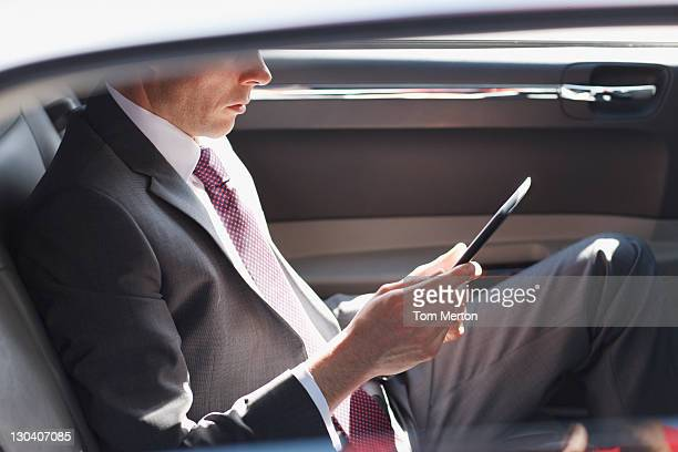 Politician reading in backseat of car