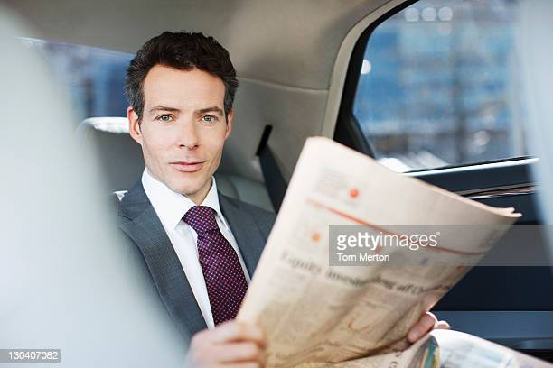 Politician reading newspaper in backseat of car