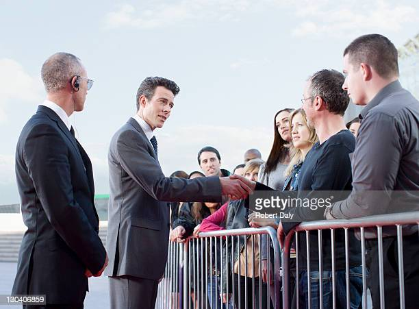politician shaking hands with people behind barrier - politician stock pictures, royalty-free photos & images