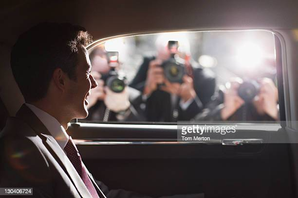 politician smiling for paparazzi in backseat of car - beroemdheden stockfoto's en -beelden