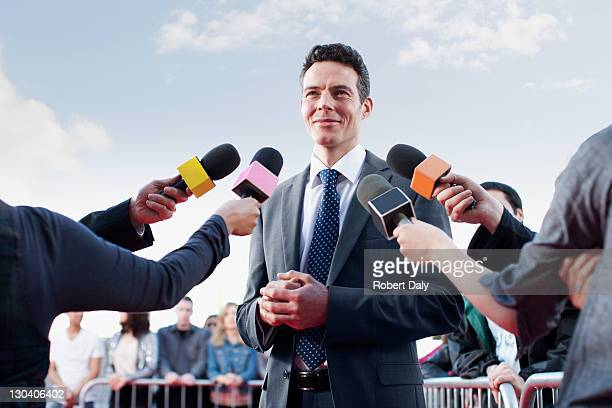 politician speaking to reporters - democratie stockfoto's en -beelden