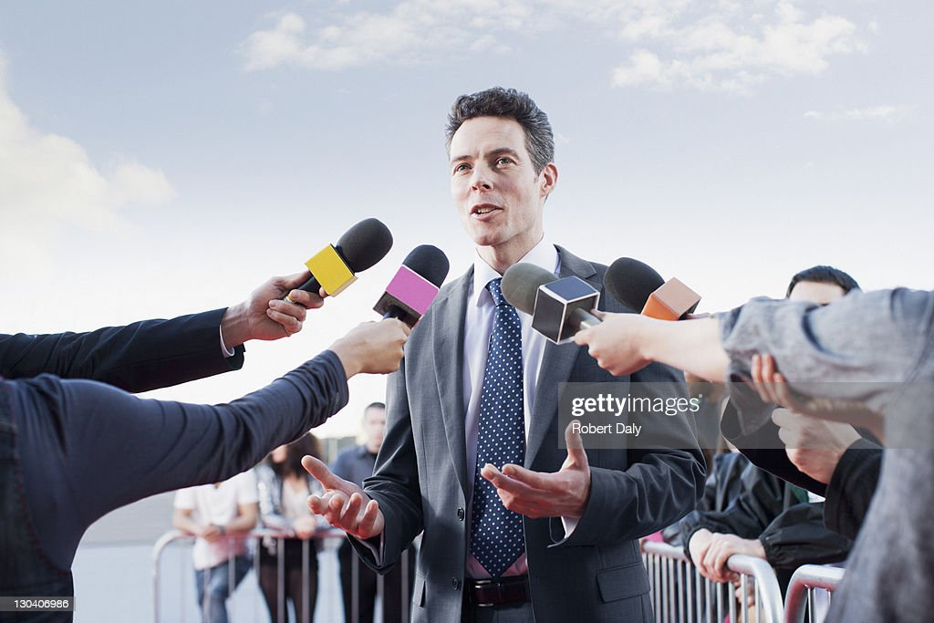 Politician talking into reporters' microphones : Stock Photo