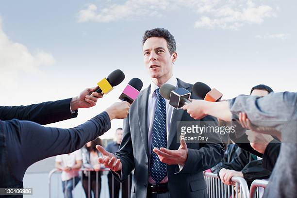 politician talking into reporters' microphones - press conference stock pictures, royalty-free photos & images