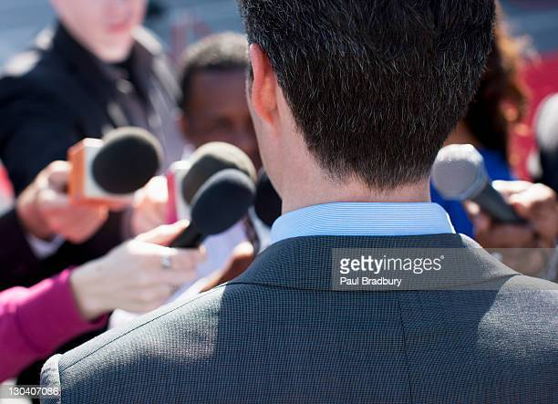 politician talking into reporters' microphones - politician stock pictures, royalty-free photos & images