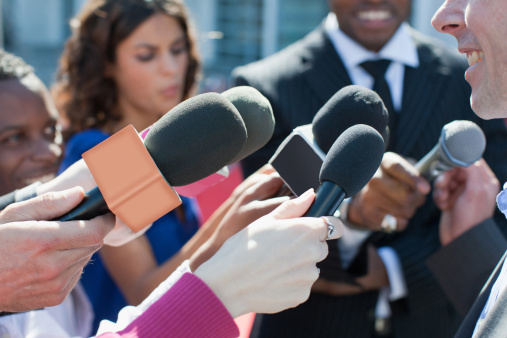 Politician talking into reporters' microphones 168961271