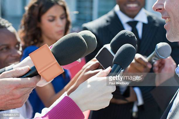 politician talking into reporters' microphones - de media stockfoto's en -beelden