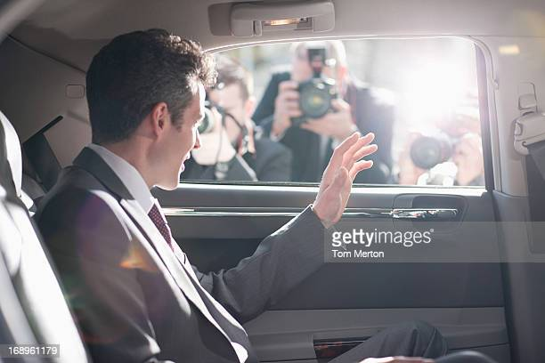 Politician waving from backseat of car