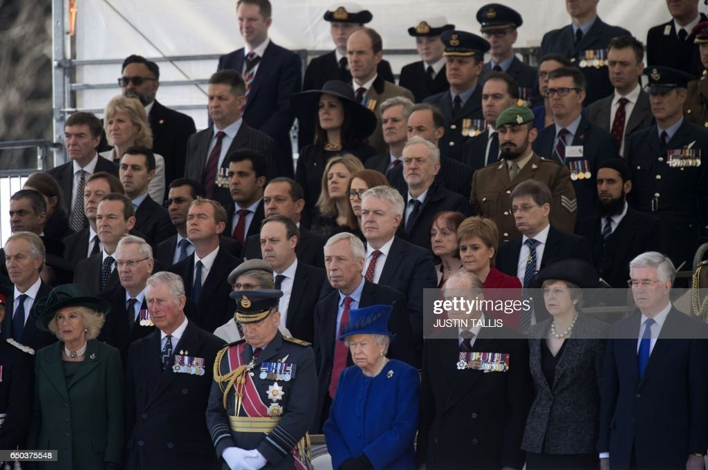 Politicians and dignitaries including (front row L-R) Britain's Camilla, Duchess of Cornwall, Britain's Prince Charles, Prince of Wales, Air Chief Marshal, Sir Stuart Peach, chief of the defence staff, Britain's Queen Elizabeth II, Britain's Prince Philip, Duke of Edinburgh, British Prime Minister Theresa May and British Defence Secretary Michael Fallon attend a Service of Commemoration and Drumhead Service on Horse Guards Parade in central London on March 9, 2017, which honours the service and duty of both the UK Armed Forces and civilians in the Gulf region, Iraq and Afghanistan, and those who supported them back home, from 1990-2015. After the Drumhead Service, The Queen will officially unveil The Iraq and Afghanistan memorial. / AFP PHOTO / Justin TALLIS