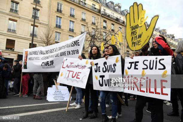 Politicians and others stand behind banners as they prepare to take part in a slient march in Paris on March 28 in memory of Mireille Knoll an...