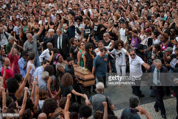 Politicians friends and relatives carry the coffin of slain Brazilian councilwoman and activist Marielle Franco during her funeral at Rio de...