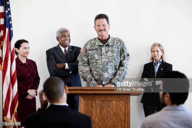 Politicians standing at podium with soldier