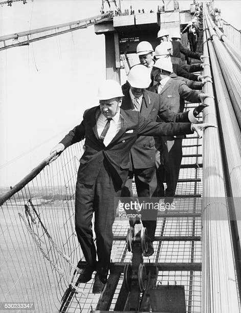 Politicians wearing hardhats as they walk along the walkway on top of the Severn Bridge lead by Transport Minister Ernest Marples June 23rd 1964