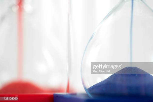politics concept - red and blue hourglasses filling up with sand - conservative party uk stock pictures, royalty-free photos & images