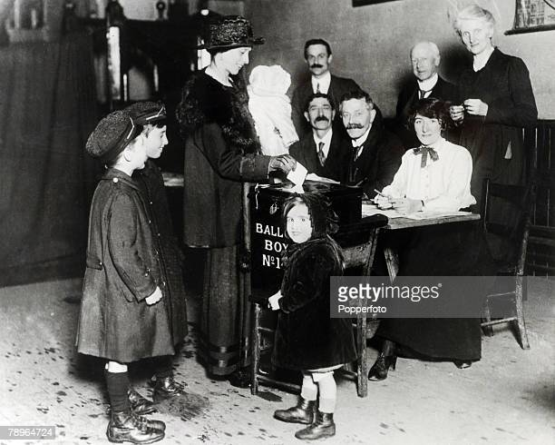 Politics England A lady with her family places her vote in the ballot box during the 1918 British General Election The Returning Officers are seated...