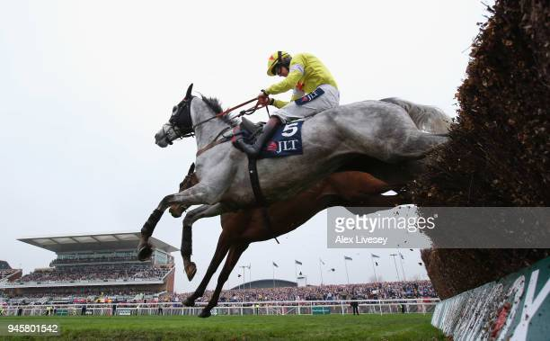Politologue ridden by Sam TwistonDavies clears the last fence alongside Min ridden by Paul Townend on their way to winning the JLT Melling Chase on...