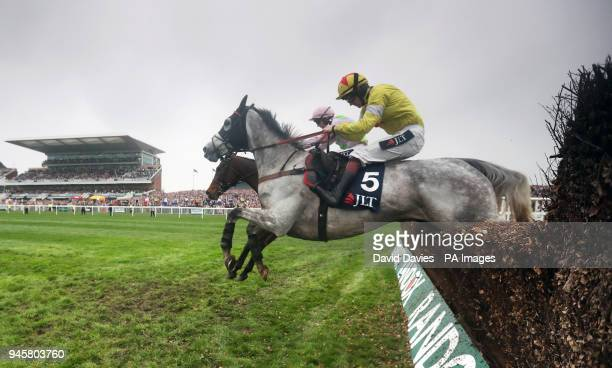 Politologue ridden by Sam TwistonDavies jumps a fence before winning the JLT Melling Chase ahead of Min ridden by Paul Townend during Ladies Day of...