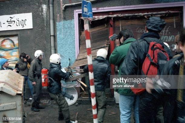 Polizisten verschaffen sich Zugang zu einem verbarrikardierten Haus. Rechts Pressefotografen, die das Geschehen fotografisch festhalten. Mit neuen...