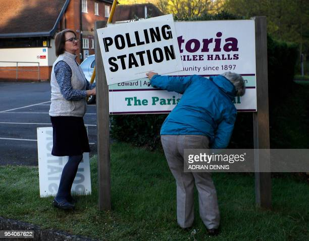 Poll clerks hang a polling station sign outside the Victoria and Jubilee Halls in Hartley Wintney Hampshire some 45 miles west of London on May 3...