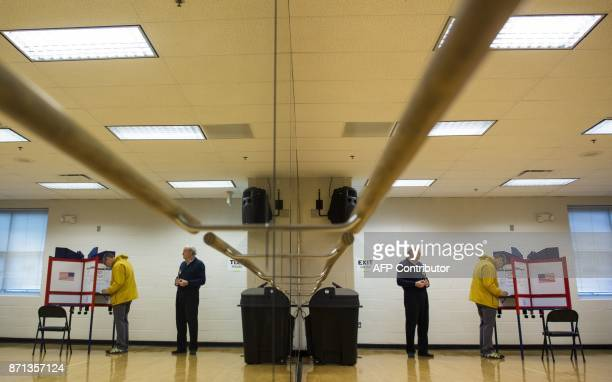 A poll volunteer waits for a man to cast his vote at a polling station in Arlington Virginia on November 7 2017 In New Jersey and Virginia voters...