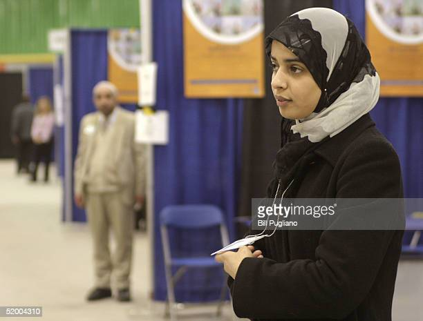 Poll worker Abeer Al-Zayadi of Dearborn, Michigan waits for new voters to register at her polling station at the designated voter registration site...