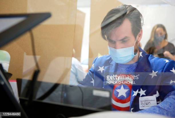 Poll worker Byron Rae works behind protective plexiglass on Election Day at downtown Summerlin on November 3 in Las Vegas, Nevada. - Americans were...
