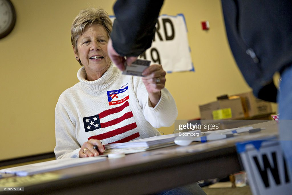 A poll worker checks the identification of a resident at polling location during the presidential primary vote in Waukesha, Wisconsin, U.S., on Tuesday, April 5, 2016. Wisconsin voters went to the polls Tuesday to decide whether Donald Trump's latest self-inflicted wounds are deep enough to deny him a win in the state's Republican primary, and, in turn, to diminish his hopes of winning the presidential nomination. Photographer: Daniel Acker/Bloomberg via Getty Images