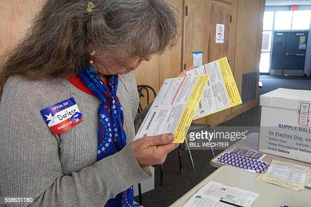 Poll worker Darlene Farnes examines some mailin ballots at a polling station at a high school June 7 2016 in San Diego California / AFP / Bill Wechter