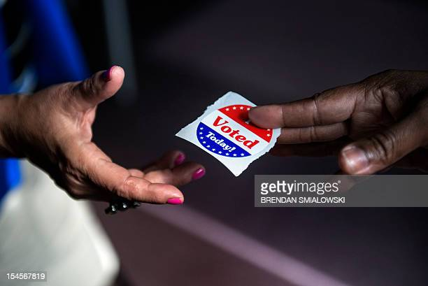 A poll worker hands out I Voted Today stickers during the first day of early voting October 22 2012 in Washington DC Citizens of the District of...