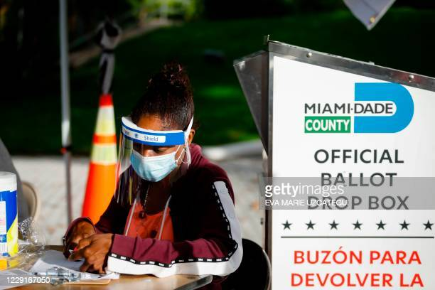 Poll worker is seen at a ballot drop box outside Miami Beach City Hall in Miami Beach, Florida on October 19, 2020. - President Donald Trump lashed...