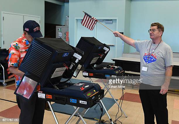 Poll worker Jim Callahan uses an American flag to direct voters to available voting machines at a polling station at John W. Bonner Elementary School...