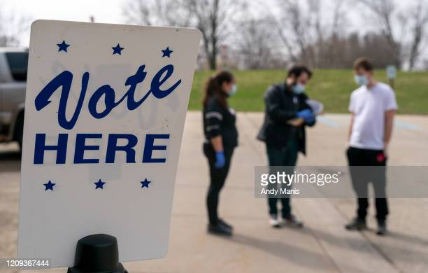 Poll worker Josh Harrison center works with Chad Donahue right during curbside voting on April 7 2020 in Madison Wisconsin Residents in Wisconsin...