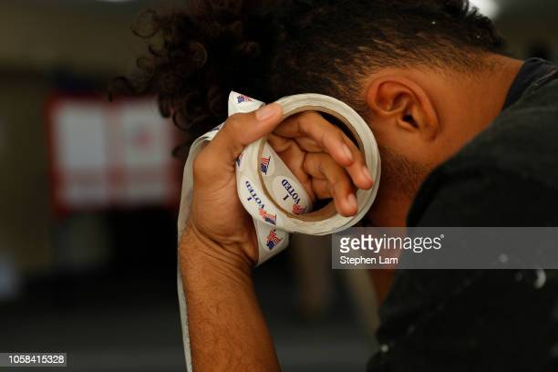 Poll worker Landen Lucas holds a roll of I Voted stickers at a polling place for California's 10th Congressional District at Modesto Covenant Church...