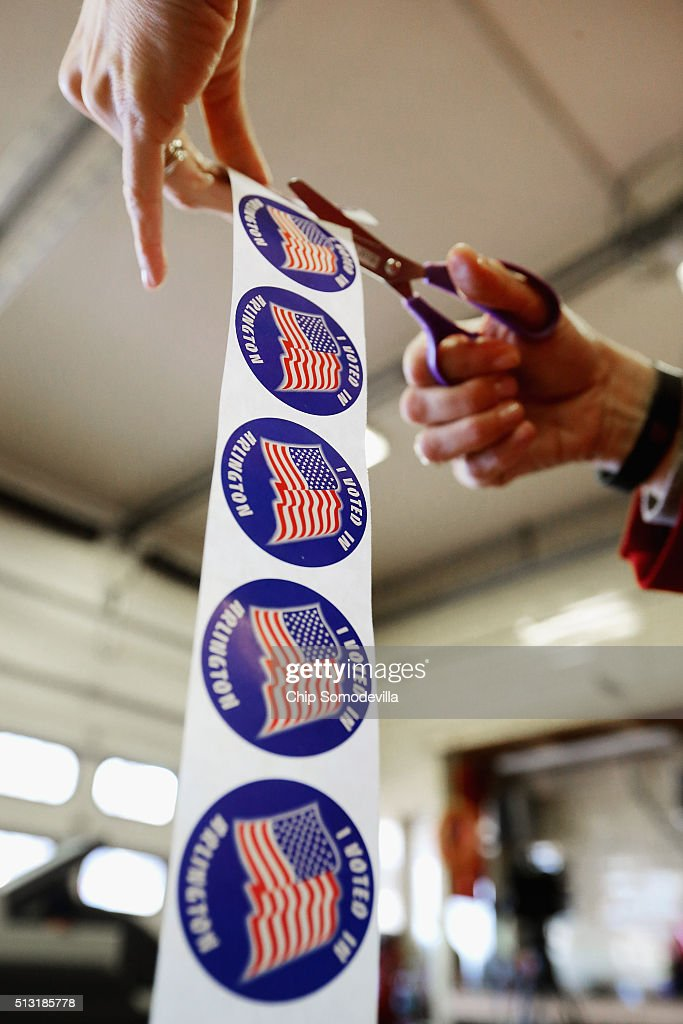 Poll worker Laura Villalba cuts a roll of stickers she will give to voters after they cast their ballots inside the Arlington County Fire Station 10 during Super Tuesday voting March 1, 2016 in Arlington, Virginia. Officials are expecting a record turnout of voters in Virginia, one of a dozen states holding presidential primaries or caucuses.