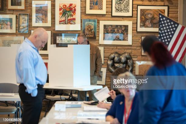 Poll worker prepares a paper ballot at Myers Park High School during the North Carolina primary on Super Tuesday in Charlotte, North Carolina on...